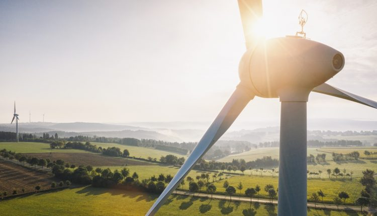 wind-turbine-and-agricultural-fields-on-a-summer-day-energy-production-with-clean-and-renewable-energy-aerial-shot