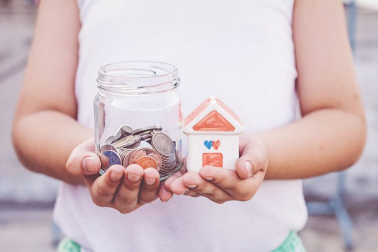 small-kid-hands-holding-house-and-coins
